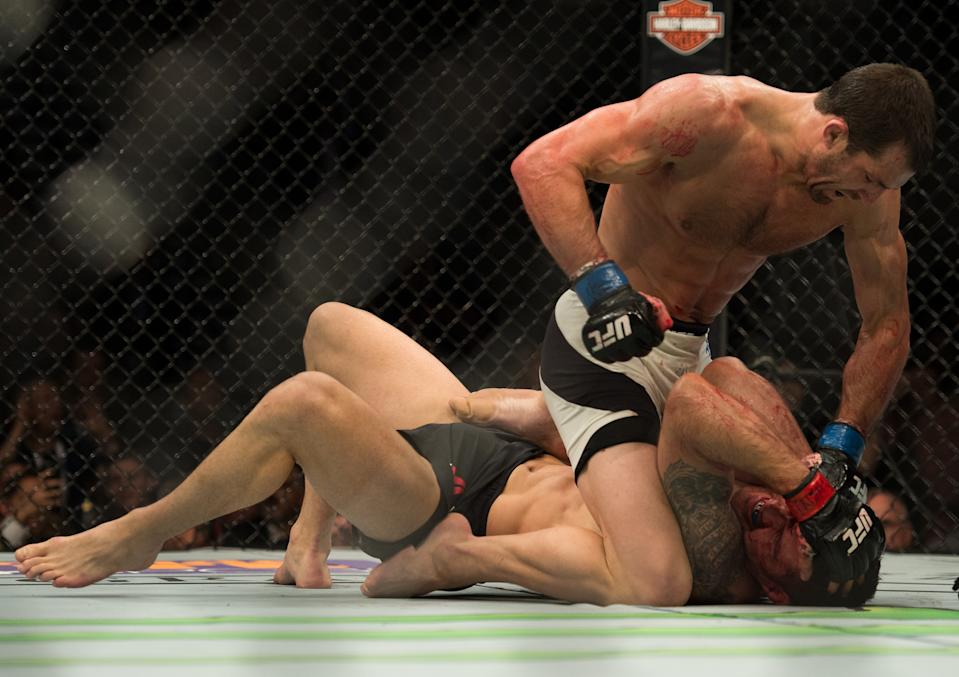 LAS VEGAS, NV - DECEMBER 12: Luke Rockhold (top) punches Chris Weidman in their middleweight title fight during the UFC 194 event inside MGM Grand Garden Arena on December 12, 2015 in Las Vegas, Nevada.  (Photo by Brandon Magnus/Zuffa LLC/Zuffa LLC via Getty Images)