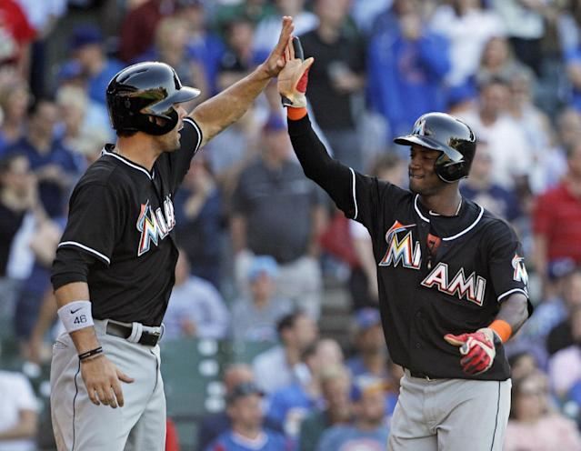Miami Marlins' Garrett Jones, left, and Adeiny Hechavarria celebrate after scoring on a two-run single hit by Reed Johnson during the ninth inning of a baseball game against the Chicago Cubs in Chicago, Friday, June 6, 2014. (AP Photo/Nam Y. Huh)