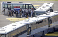 People disembark from a chartered plane and board waiting busses, after being evacuated from Afghanistan, during arrival at Melsbroek Military Airport in Melsbroek, Belgium, Wednesday, Aug. 25, 2021. (AP Photo/Olivier Matthys)