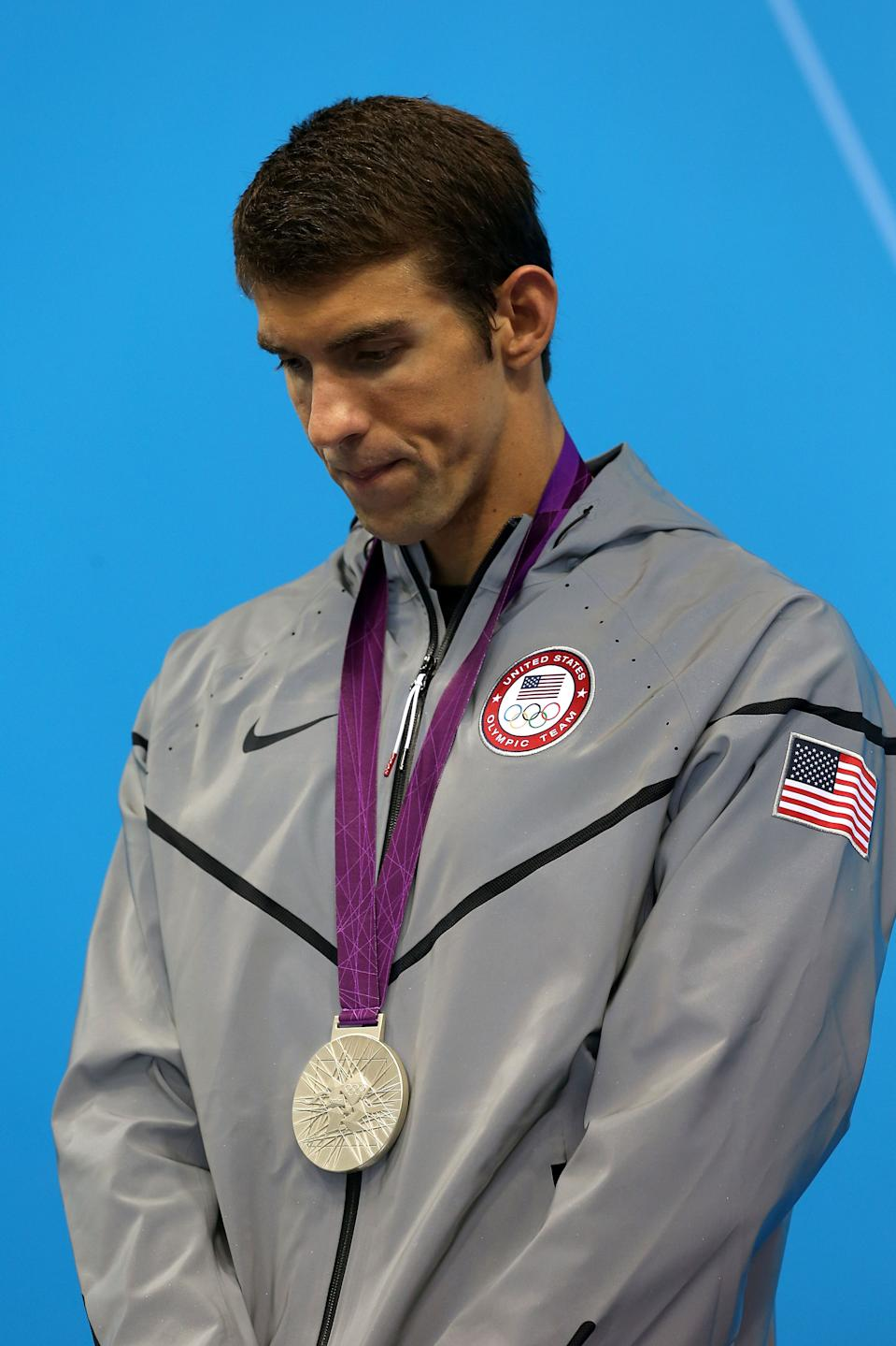 LONDON, ENGLAND - JULY 31: Silver medallist Michael Phelps of the United States poses on the podium during the medal ceremony for the Men's 200m Butterfly final on Day 4 of the London 2012 Olympic Games at the Aquatics Centre on July 31, 2012 in London, England. (Photo by Clive Rose/Getty Images)