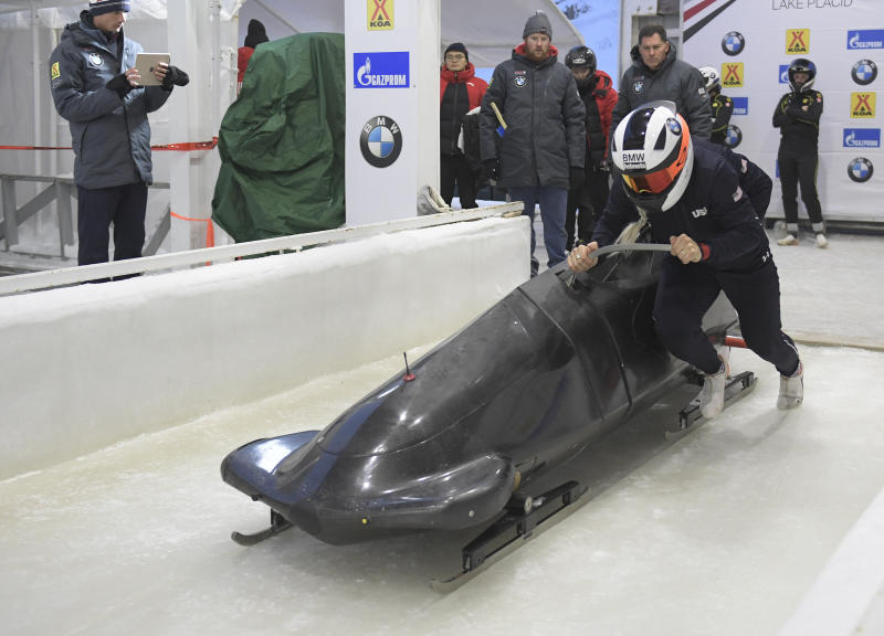 Kaillie Humphries, formerly of team Canada but now representing The United States, front, pushes her sled at the start of a training run for the women's World Cup bobsled event in Lake Placid, N.Y., on Friday, Dec. 6, 2019. Competition begins on Saturday. (AP Photo/Hans Pennink)