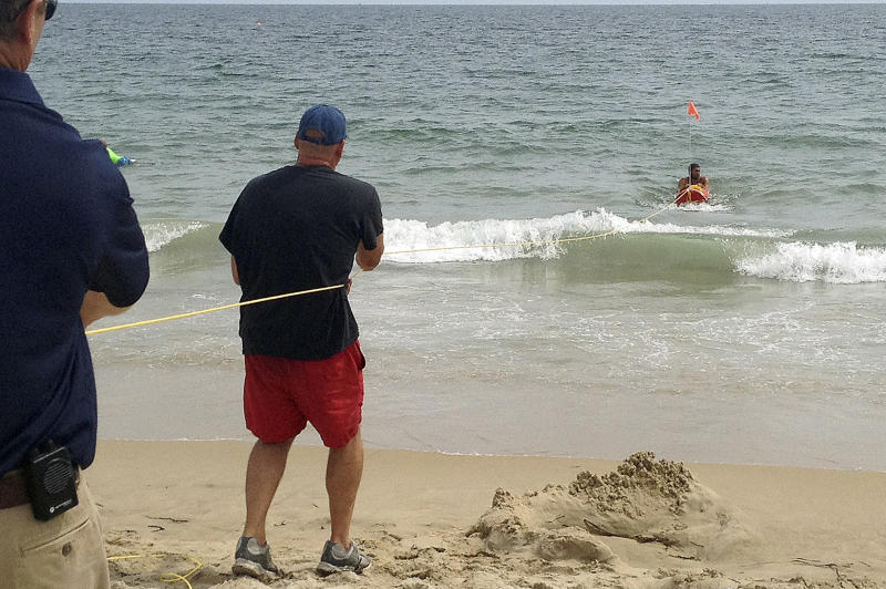 In this Wednesday, Aug, 8, 2012 photo, Misquamicut, R.I., Fire Chief Louis Misto, far left, and lifeguard Jeff Lenihan, center, demonstrate a rescue technique with the EMILY remote-control lifesaving device as lifeguard Philip Campo, in water at right, holds on to the apparatus at Old Town Beach, in Westerly, R.I. EMILY is an acronym for Emergency Integrated Lifesaving Lanyard. (AP Photo/Michelle R. Smith)