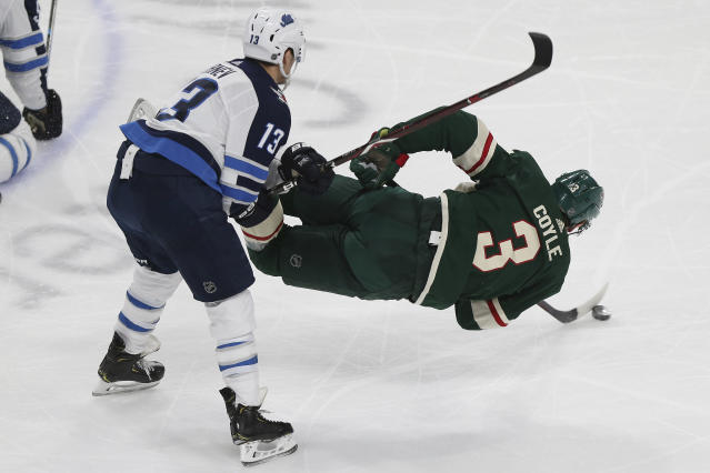 Minnesota Wild's Charlie Coyle tries to control the puck while airborne against Winnipeg Jets' Brandon Tanev in the third period of an NHL hockey game Thursday, Jan. 10, 2019, in St. Paul, Minn. (AP Photo/Stacy Bengs)