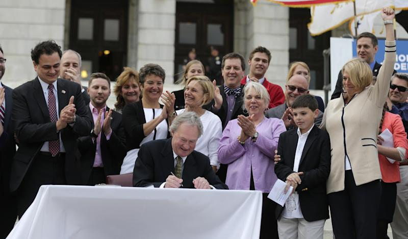 Rhode Island Gov. Lincoln Chafee signs a gay marriage bill into law outside the State House in Providence, R.I., Thursday, May 2, 2013. (AP Photo/Charles Krupa)