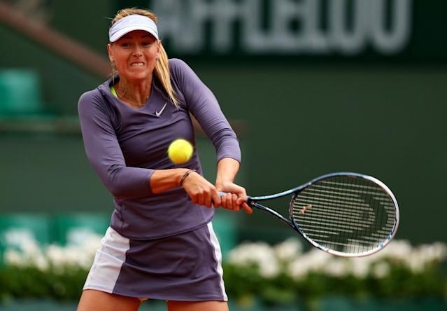 PARIS, FRANCE - MAY 30: Maria Sharapova of Russia plays a backhand in her Women's Singles match against Eugenie Bouchard of Canada during day five of the French Open at Roland Garros on May 30, 2013 in Paris, France. (Photo by Clive Brunskill/Getty Images)