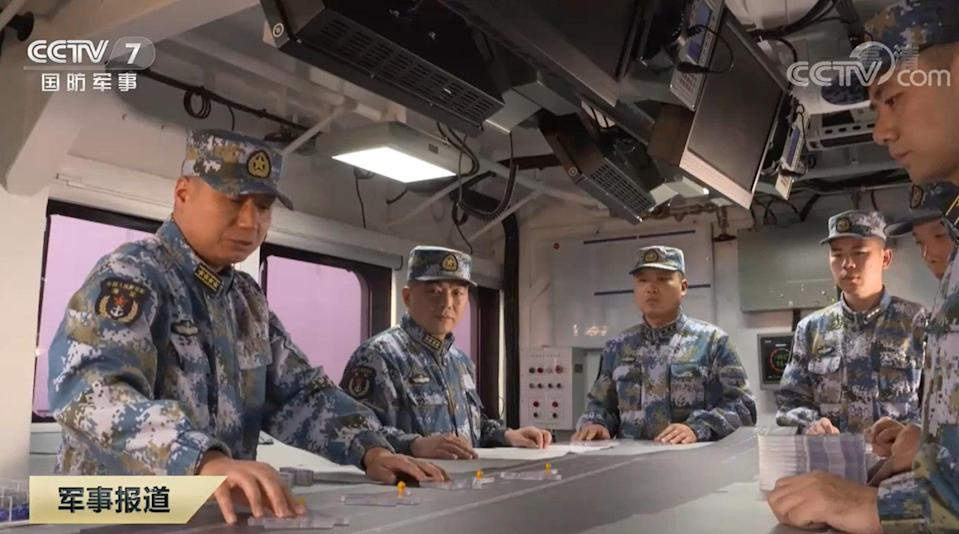 "Lai Yijun, captain of the Shandong (left), and political commissar Song Wenjun (second left) play ""carrier chess"" using models of J-15 fighters. Photo: CCTV"