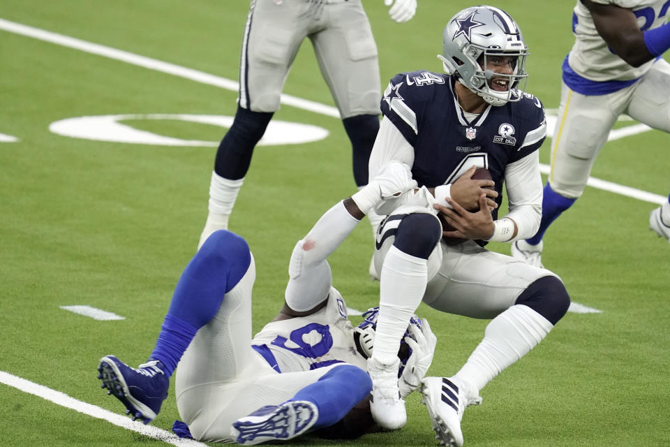 Dallas Cowboys quarterback Dak Prescott, right, is tackled by Los Angeles Rams defensive end Michael Brockers. (AP Photo/Jae C. Hong )
