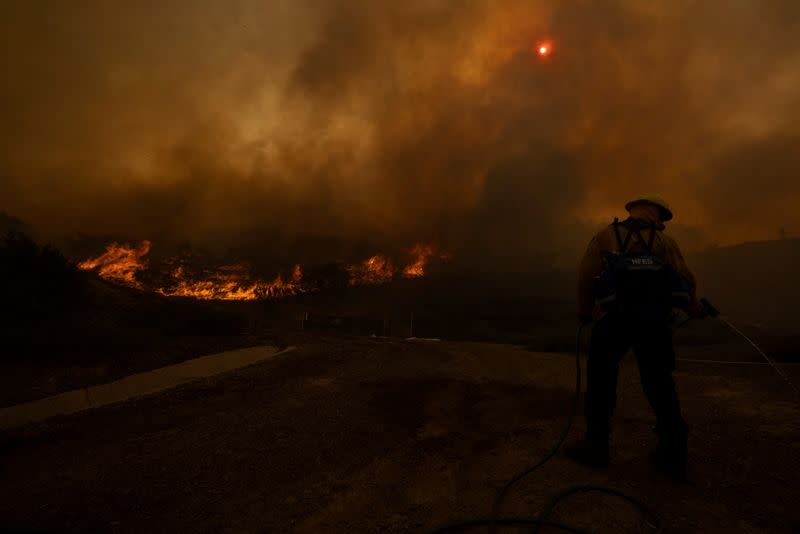 A firefighter uses a homeowners garden hose to help battle the Silverado Fire, a wind driven wildfire near Irvine, California