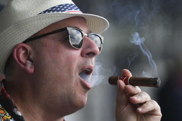 A man smokes a cigar ahead of the Preakness Stakes horse race at Pimlico Race Course, Saturday, May 15, 2021, in Baltimore. (AP Photo/Will Newton)