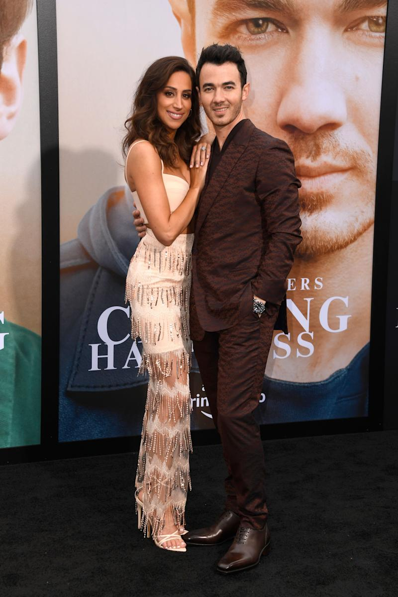 Kevin Jonas and his wife stand at the premiere for a film