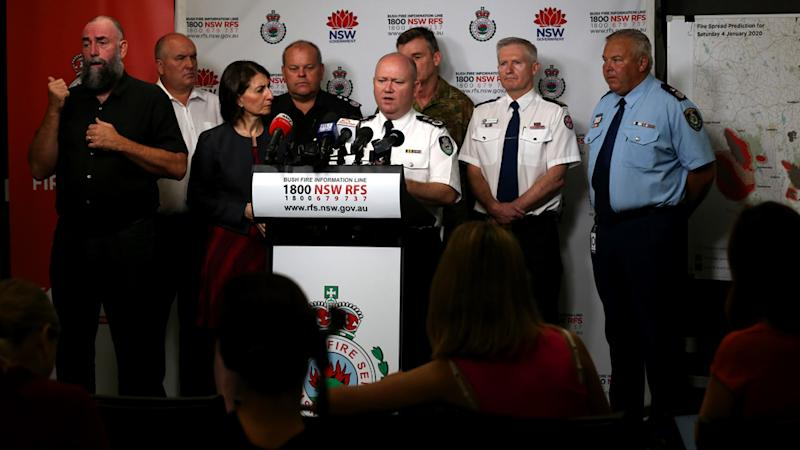 RFS Commissioner Shane Fitzsimmons (middle) speaks to reporters in Sydney providing an update on conditions as NSW and Victoria brace for a day of extreme fire danger.