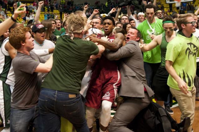 In this Thursday, Feb. 27, 2014 photo, New Mexico State's Daniel Mullings, at center in red and white jersey, is involved in a brawl involving players and fans who came onto the court when New Mexico State guard K.C. Ross-Miller hurled the ball at Utah Valley's Holton Hunsaker seconds after the Wolverines' 66-61 overtime victory against the Aggies in Orem, Utah. (AP Photo/The Daily Herald, Grant Hindsley)