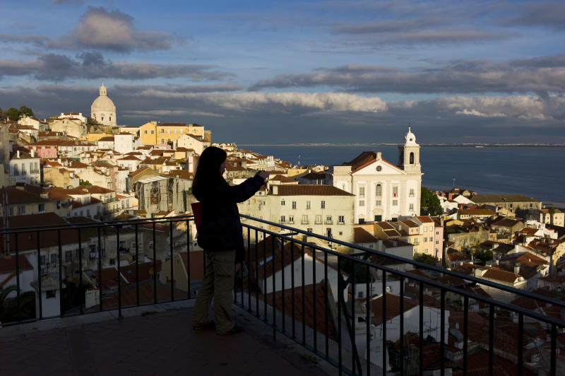 In this photo taken Dec. 18 2012, a tourist takes photos from a viewpoint overlooking Lisbon's Alfama neighborhood and the Tagus river. The Alfama quarter is distinguished by its narrow, cobbled streets on the hillside below Lisbon castle, where archaeologists have found traces of occupation dating from the seventh century B.C. (AP Photo/Armando Franca)