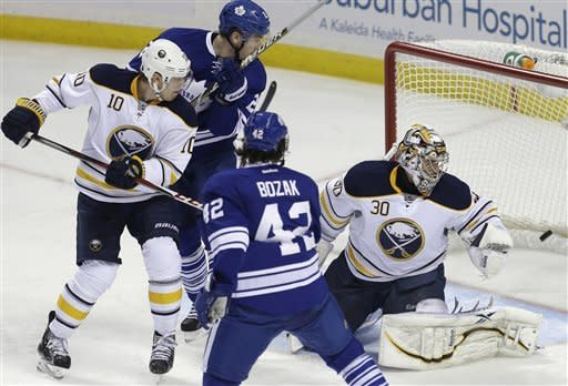 Toronto Maple Leafs' Cody Franson, not shown, scores on Buffalo Sabres' Ryan Miller under pressure from Maple Leafs' Tyler Bozak and James van Riemsdyk (21) as Sabres' Christian Ehrhoff (10) defends during the second period of an NHL hockey game in Buffalo, N.Y., Tuesday, Jan. 29, 2013. (AP Photo/David Duprey)