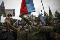 Azerbaijani soldiers hold national flags and a portrait of Azerbaijani President Ilham Aliyev as they celebrate the transfer of the Lachin region to Azerbaijan's control, as part of a peace deal that required Armenian forces to cede the Azerbaijani territories they held outside Nagorno-Karabakh, in Aghjabadi, Azerbaijan, Tuesday, Dec. 1, 2020. Azerbaijan has completed the return of territory ceded by Armenia under a Russia-brokered peace deal that ended six weeks of fierce fighting over Nagorno-Karabakh. Azerbaijani President Ilham Aliyev hailed the restoration of control over the Lachin region and other territories as a historic achievement. (AP Photo/Emrah Gurel