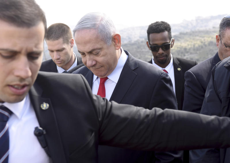 Israeli Prime Minister Benjamin Netanyahu, center, surrounded by bodyguards, walks to get an overview of the West Bank Israeli settlement of Har Homa where he announced a new neighborhood is to be built, Thursday, Feb. 20, 2020. (Debbie Hill/Pool via AP)