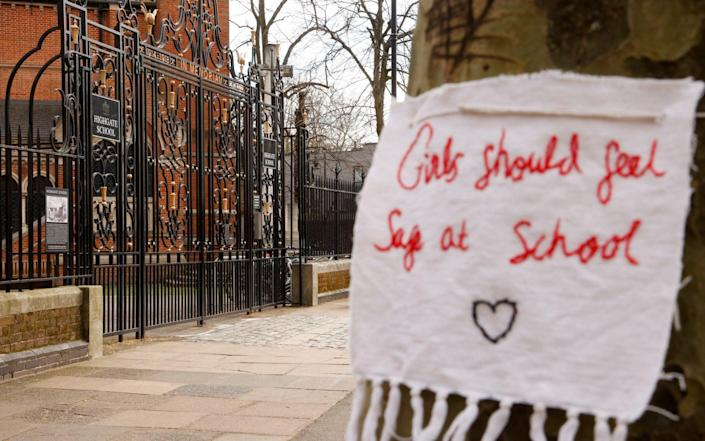 A sign attached to a tree outside the entrance to Highgate School, in London - John Sibley/Reuters