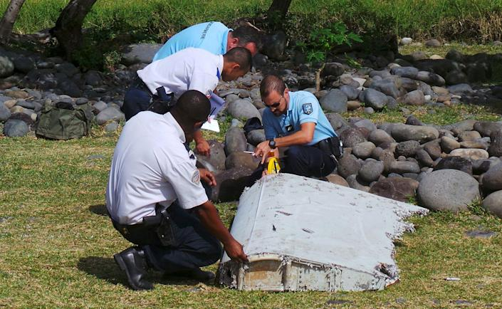 File picture shows French gendarmes and police inspecting a large piece of plane debris which was found on the beach in Saint-Andre, on the French Indian Ocean island of La Reunion, July 29, 2015. French prosecutor announced on Thursday that we can say with certainty that the wing part found on Saint-Andre beach was from missing Malaysia Airlines Flight MH370. REUTERS/Zinfos974/Prisca Bigot/Files TPX IMAGES OF THE DAY