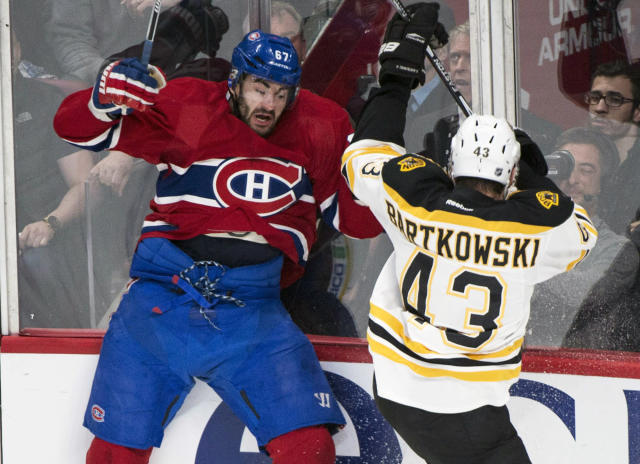 Montreal Canadiens' Max Pacioretty, left, is checked into the boards by Boston Bruins' Matt Bartkowski during the first period of a second-round NHL playoff hockey game on Monday, May 12, 2014, in Montreal. (AP Photo/The Canadian Press, Paul Chiasson)