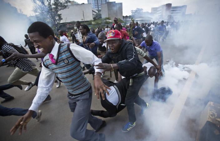 Opposition supporters flee from tear gas grenades fired by riot police, during a protest in downtown Nairobi, Kenya, May 16, 2016. Kenyan police have tear-gassed and beaten opposition supporters during a protest demanding the disbandment of the electoral authority over alleged bias and corruption. (AP Photo/Ben Curtis)