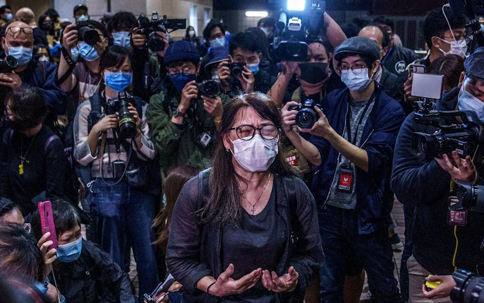 Adoptive mother of Hendick Lui Chi Hang, one of the charged activists, speaks to the media at West Kowloon Magistrates Courts following a hearing for 47 opposition activists charged with violating the city's national security law - Lam Yik/Bloomberg