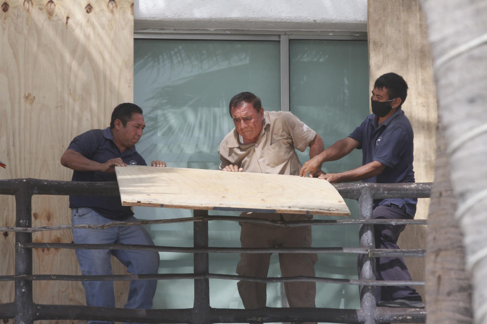 Beach hotel workers cover doors and windows with plywood as they prepare for the arrival of Tropical Storm Zeta in Playa del Carmen, Mexico, Monday, Oct. 26, 2020. A strengthening Tropical Storm Zeta is expected to become a hurricane Monday as it heads toward the eastern end of Mexico's resort-dotted Yucatan Peninsula and then likely move on for a possible landfall on the central U.S. Gulf Coast at midweek. (AP Photo/Tomas Stargardter)