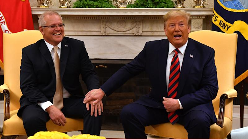 Donald Trump puts his hand on top of Scott Morrison's during a press call at the White House.