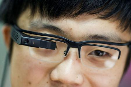 LLVision design director Tianyi Liu wears LLVision facial recognition smart glasses as he demonstrates them at the company's office in Beijing, China February 28, 2018. Picture taken February 28, 2018. REUTERS/Thomas Peter