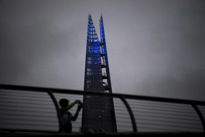 A man takes a picture on the Millennium Bridge as the Shard is lit up in blue in support of the National Health Service (NHS), as the capital is set to reopen after the lockdown due to the coronavirus outbreak, in London, Saturday, July 4, 2020. England is embarking on perhaps its biggest lockdown easing yet as pubs and restaurants have the right to reopen for the first time in more than three months. In addition to the reopening of much of the hospitality sector, couples can tie the knot once again, while many of those who have had enough of their lockdown hair can finally get a trim. (AP Photo/Alberto Pezzali)