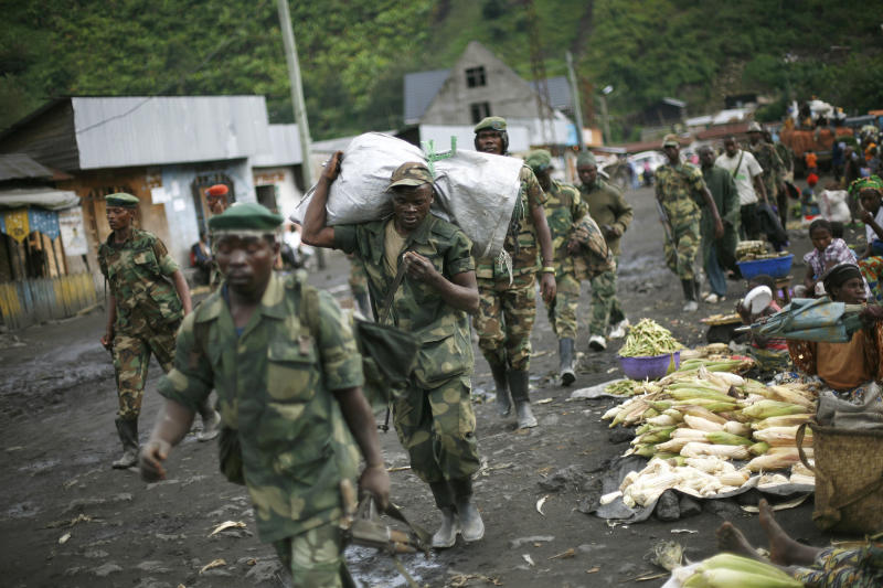 """FILE - In this Nov. 30, 2012 file photo, M23 rebels withdraw from the Masisi and Sake areas in the eastern Congo town of Sake, some 27 kms west of Goma, Congo. A Congolese rebel group whose fighters retreated into Uganda after being hammered by U.N.-backed Congolese government forces """"can still regroup,"""" a Ugandan government spokesman said Tuesday, Nov. 12, 2013. The warning came after Congolese government officials delayed signing a peace accord with the insurgents. (AP Photo/Jerome Delay, File)"""