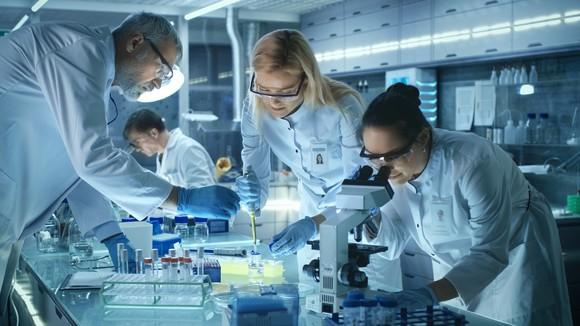 Four people working in a laboratory.