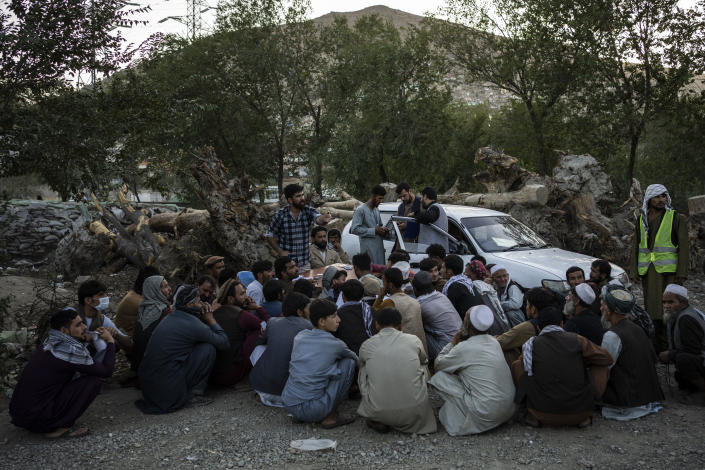 Displaced Afghans wait for food donations at a camp for internally displaced persons in Kabul, Afghanistan, Monday, Sept. 13, 2021. (AP Photo/Bernat Armangue)