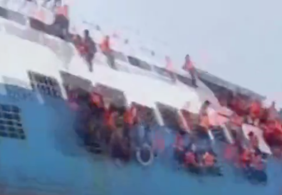 <em>Terrified – dramatic footage shows people clinging on to the side of the ferry as it sinks off the coast of Indonesia (Picture: Reuters)</em>