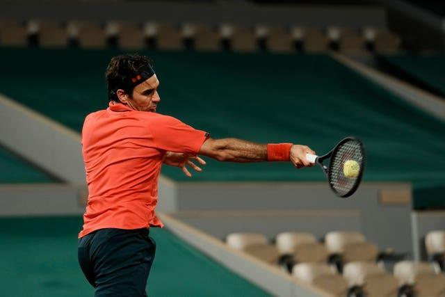 Roger Federer hits a forehand in front of an empty stadium