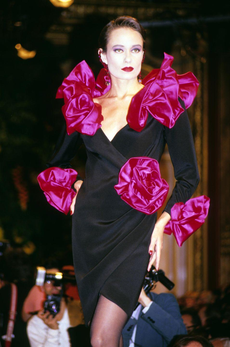 <p>A model in a little black dress complete with pink pouf detailing at Yves Saint Laurent's runway show during Paris Fashion Week.</p>