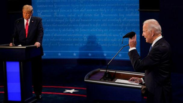 PHOTO: Former Vice President Joe Biden holds up a mask as President Donald Trump takes notes during the second and final presidential debate at the Curb Event Center at Belmont University in Nashville, Tenn., Oct. 22, 2020. (Morry Gash/Pool via Reuters)