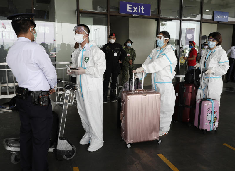 Foreigners wear protective suits as they enter the departure area of Manila's International Airport, Philippines on Friday, May 22, 2020. Some airlines began flights in and out of the country as the capital eases it's lockdown while it continues to fight the spread of the new coronavirus. (AP Photo/Aaron Favila)