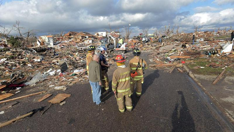 Washington, Ill., firefighters stand in the middle of Devonshire Street on the North side of Washington, Ill., after a tornado leveled at least fifty homes, Sunday, Nov. 17, 2013. High winds that followed the tornado are causing danger as homeowners and emergency workers try to search homes. (AP Photo/The Pantagraph, Steve Smedley)