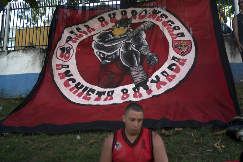 A soccer fan sits in front a giant banner depicting a vulture, the Flamengo's mascot, during the funeral of Samuel de Souza Rosa, one of the 10 young soccer players killed in a fire at the training ground of Brazilian soccer club Flamengo, in Sao Joao de Meriti, Brazil, Monday, Feb. 11, 2019. The death of de Souza Rosa and his teammates has shed a tragic light on the state of shoddy infrastructure and lax oversight in Latin America's largest nation. (AP Photo/Leo Correa)