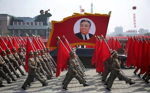 North Korean soldiers carry flags and a photo of late leader Kim Il Sung during a military parade  - Credit: AP Photo/Wong Maye-E