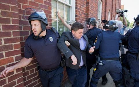 Police escort Jason Kessler, organizer of the 'Unite the Right' rally, as he is rushed away after a press conference at City Hall in Charlottesville, Virginia - Credit: EPA