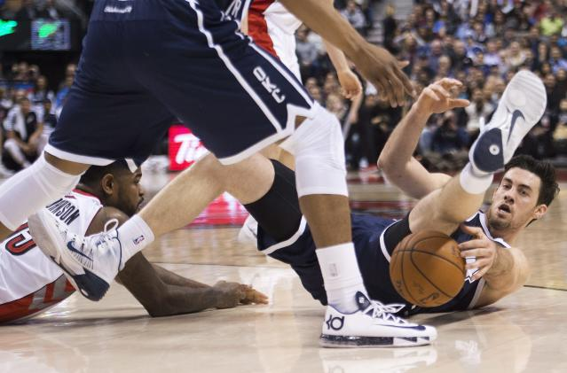 Toronto Raptors' Amir Johnson, left, battles for the loose ball against Oklahoma Thunder forward Nick Collison, right, during the first half of an NBA basketball game in Toronto on Friday, March 21, 2014. (AP Photo/The Canadian Press, Nathan Denette)