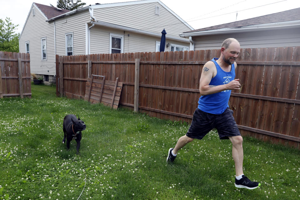 Christian Hainds plays with his dog, Reyna in the backyard of his home in Hammond, Ind., Monday, June 7, 2021. Health officials have warned since early on in the pandemic that obesity and related conditions such as diabetes were risk factors for severe COVID-19. It wasn't until he was diagnosed as diabetic around the start of the pandemic that he felt the urgency to make changes. Hainds lost about 50 pounds during the pandemic, and at 180 pounds and 5 feet, 11 inches tall is no longer considered obese. (AP Photo/Shafkat Anowar)