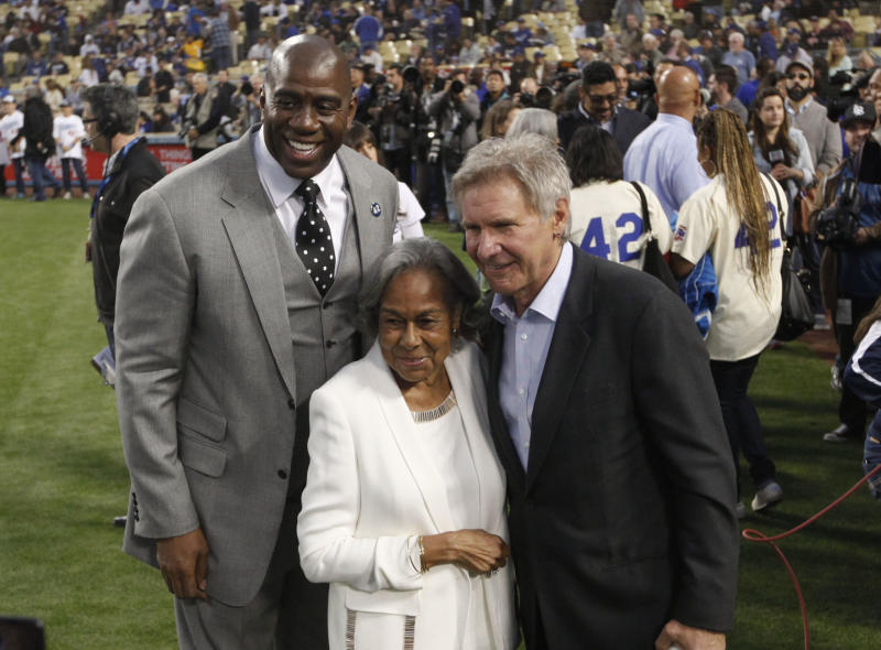 Los Angeles Dodgers owner Magic Johnson, left, Rachel Robinson, widow of baseball player Jackie Robinson, center, and actor Harrison Ford pose for photos during a Jackie Robinson Day ceremony before a baseball game against the San Diego Padres in Los Angeles, Monday, April 15, 2013. (AP Photo/Jae C. Hong)