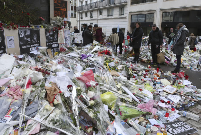 FILE - In this Jan. 14, 2015 file photo, flowers lay outside Charlie Hebdo headquarters in Paris. The January 2015 attacks against Charlie Hebdo and, two days later, a kosher supermarket, touched off a wave of killings claimed by the Islamic State group across Europe. Seventeen people died along with the three attackers. Thirteen men and a woman accused of providing the attackers with weapons and logistics go on trial on terrorism charges Wednesday Sept. 2, 2020. (AP Photo/Jacques Brinon, File)