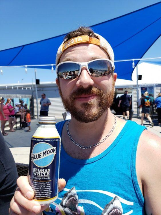 Man in sunglasses smiling holding a can of Blue Moon beer