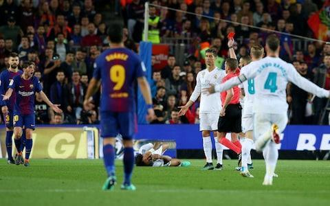 "Lionel Messi helped 10-man Barcelona remain undefeated in the Spanish league after drawing 2-2 with Real Madrid on Sunday in a testy El Clasico that saw Cristiano Ronaldo substituted at half-time with a leg injury. Ronaldo hurt his lower right leg while canceling out Luis Suarez's opener in the 10th minute. Gerard Pique stepped on his ankle as he unsuccessfully tried to stop the Madrid forward from scoring from close range. Ronaldo played on until half-time, when he was replaced by Marco Asensio. Madrid were dominating the match at Camp Nou and Barcelona right back Sergi Roberto was shown a direct red card in first-half injury time for swiping his hand at Marcelo's face as tempers flared between the rivals. But that was when Messi came to the hosts' rescue, sending the ball past Keylor Navas in the 52nd to swing the match back in Barcelona's favor despite playing a man down. Luis Suarez opens the scoring for Barcelona Credit: AP Gareth Bale pulled Madrid level again in the 72nd minute after curling in a pass by Asensio. Messi had more chances to grab the late winner but was denied by Navas. Barcelona remain unbeaten after 35 league matches this season and extended their record run to 42 Liga games without a loss. Their last league defeat came at Malaga in April 2017. Barcelona have matches left against Villarreal, Levante and Real Sociedad to try to become the first team to go unbeaten in the competition since the 1930s, when it consisted of merely 10 teams. Ronaldo, l'inquiétude https://t.co/sRHGHNM6eEpic.twitter.com/f4WLWR1fyD— L'actu du Sport (@LactuDuSport) May 6, 2018 Zinedine Zidane refused to put a time frame on Cristiano Ronaldo's injury absence. ""I don't know how long he'll be out,"" the manager said. ""He said it wasn't much, but we'll see tomorrow. ""We'll do some tests to see the extent of the damage done to his ankle. He was a little worried because it was a bit swollen, but he said that it's nothing serious."" 9:42PM FULL-TIME: BARCELONA 2-2 REAL MADRID Another corner! Ramos however commits a foul, and Barcelona's unbeaten record remains intact! Plenty of spice in this one as expected, Sergi Roberto's red card before the break leaving Barcelona down to 10 men for the second half. Fine finish by Gareth Bale brought Real back into the contest for the second time at 2-2, with Barcelona's defence then holding firm. Credit: AFP 9:40PM 90+4 mins Paulinho loses possession - here come Real. Bale from range, deflected. The visitors will have a corner. 9:39PM 90+3 mins Barcelona unsure whether to thump a free-kick into the box or go to the corner and grind down the clock. They opt for the former but Real clear. Barcelona seconds away from maintaining this unbeaten run in the league. 9:36PM 90 mins More last-ditch defending from Pique as Barca hang on. Four minutes of added time coming up. Suarez (slowly) heads off to be replaced by Alcacer. 9:32PM 86 mins Crowd not happy as Real continue to attack despite Suarez being down with an injury after colliding with Ramos. Hard to tell if he's seriously hurt, wasn't a lot of contact, after Vazquez puts the ball out. Credit: REUTERS 9:30PM 84 mins Final change for Real, Kovacic on for Kroos. It's also his 24th birthday, so naturally we despise him for being so young. 9:26PM 80 mins Real on top, pinning Barcelona back. The hosts' unbeaten record hanging on by a thread here. Modric shoots well over the bar. 9:22PM 77 mins Bale and then Marcelo head into the book, the latter for complaining to the official. Bale's arguably lucky to still be out there. Marcelo denied a penalty a few minutes earlier after a collision with Jordi Alba, which looked like a penalty on the replay. 9:19PM GOOOOAAALLL BALE! BARCELONA 2-2 REAL MADRID Stunning finish by Bale! Wraps his foot around it and Ter Stegen never had a prayer, buried in the top left corner. We're level again! Credit: SKY SPORTS Brilliant goal from Bale. What a game.— Gary Lineker (@GaryLineker) 6 May 2018 9:15PM 70 mins Messi breaks clear! Has time, trying to shoot across the goal but Navas is up to the task and parries it behind. That could have been game over. 9:14PM They're brought up the thousand Messi's strike made it 1000 goals between him and Ronaldo (501/499). That's utterly mental.— Gary Lineker (@GaryLineker) 6 May 2018 9:12PM 66 mins Vazquez warming up on the touchline. Just the 97,939 in attendance this Sunday evening. Crowd have livened up after the shock of that red card. 9:08PM 62 mins Messi lining up a free-kick, in range of the goal and a recovered Navas. 24 metres out... into that seven-man wall. Real clear. Credit: SKY SPORTS 9:04PM 58 mins Paulinho nearly scores with his first touch, colliding into Navas who looks to be winded. Nothing malicious, had to go with it and just caught the keeper with his boot. 9:03PM 56 mins Pique, for some reason all the way up behind Messi, tries to play a through ball but is cut off. 3-1 against a Ronaldo-less Real would probably do it. Off comes the great Iniesta, handing the captaincy to Messi. Huge ovation as expected. On comes Paulinho. Credit: SKY SPORTS 8:59PM GOAAAAALLLLLL MESSI! BARCELONA 2-1 REAL MADRID The record looks safe for now! After that Asensio shot Barca break, Suarez getting away from Varane (possibly illegally) before setting up Messi who tucks it away. Credit: SKY SPORTS 8:57PM 51 mins Iniesta, Suarez and Messi nearly combining to create a chance. Interesting to see how FCB approach this second half with that record on the line. Asensio carries the ball forward before unleashing a shot, easily saved by Navas. 8:53PM 47 mins Marcelo, dancing forward, has a shot blocked by Pique. Playing a big role in this one so far. Ronaldo apparently suffering from a slight ankle sprain. 8:51PM Ronaldo replaced at half-time Asensio comes on. That seems sensible to be honest. Barcelona's unbeaten record faces a real test with only 10 men for the second half. 8:48PM Special sponsor for Barcelona tonight Beko have been displaced on the Barcelona sleeve for the evening by #EatLikeAPro. Today we give up our logo on the @fcbarcelona jersey for #ElClasico to raise awareness of childhood obesity. Each #EatLikeAPro means we'll donate 1€ to @UNICEF in collaboration with @fundacioFCB ⬇️ pic.twitter.com/0GTReVCy4a— Beko (@Beko) 6 May 2018 8:35PM HALF-TIME: BARCELONA 1-1 REAL MADRID Ronaldo's free-kick is fired into the wall, and that'll be half-time. It's not lacked for drama, loads of chances before tempers boiled over towards the end of the half leading to Roberto's red card. Two questions: 1) How many more goals? 2) How many more reds?! Credit: REUTERS 8:33PM RED CARD SERGI ROBERTO! Into added time and there's a ton of fouls. Bale's studs catch the back of Umtiti's leg, and he's lucky not to be carded for that to be honest. Another incident off the ball and Roberto has gone! Marcelo in a heap, now miraculously up on his feet again - there's nothing in it really, a slap to the face by Roberto to Marcelo after they come together following a Roberto pass. That seems rash. 8:30PM 43 mins Suarez bristling (shocking, right?) and confronts Ramos. Just an arm to the chest. Tonight's referee Alejandro Jose Hernandez Hernandez shows a yellow card to Suarez, and then to Messi after a late challenge on Ramos. Messi not buying it. 8:26PM 40 mins Casemiro doing his best to not let Messi out of his sight. It's gone well enough up to this point. Benzema tries to cut in and curl a shot to the far post, after a run from Kroos, but he puts it wide. Real on top in midfield. Credit: REUTERS 8:22PM 37 mins Umtiti blows what looks like a massive chance after Messi chips in a free-kick, but he's clearly offside. Ronaldo doesn't look that comfortable. Does he come out for the second half with a Champions League final a few weeks away? 8:19PM 34 mins Break from Ronaldo and Benzema down the left. Barca get back in time to quell the threat though, forcing Real to retreat. Very effective defence. Real perhaps narrowly on top though. Marcelo's cross a little too deep meaning Barca can advance. 8:16PM 32 mins Modric trying to outmuscle Umtiti was never going to go well. He loses out trying to chase a Nacho through-ball. Varane yellow carded for pulling back Suarez. Then Jordi Alba and Modric (of all people?!) get into a bit of pushing and shoving, was Alba's hand round Modric's throat? Referee missed it. They've made up. 8:12PM 30 mins Modric plays through Ronaldo, saved! Four shots already for Ronaldo in this game. Credit: REUTERS 8:11PM 26 mins Ronaldo with a header on goal but Benzema was waiting in a better position at the far post. Pity. Real building into this as Kroos rushes a shot. Marcelo finding plenty of space with Coutinho not tracking back. 8:08PM 22 mins Pique slides across and gets just about enough on the ball to halt a Real break. A few of those already as just sit back and try and contain Barca before attempting to counter. 8:05PM 19 mins Quality ball over the top from Messi towards Alba, just slightly in front of him. Many more goals to come in this one. Credit: AFP 8:01PM 16 mins Slight worry that Ronaldo has picked up an injury in scoring that goal. He gets some treatment, Real temporarily playing with 10 men. He's back on trying to run it off. 8:00PM GOAL RONALDO! BARCELONA 1-1 REAL MADRID Superb! Ronaldo gets free down the left and cuts in, back-heeled to Kroos whose cross to the far post is headed back across by Benzema for Ronaldo to knock it in. We're level. Ripping start to this one. 7:58PM 12 mins Nacho into the book for a challenge from behind on Coutinho. Barca advance, shouts for a penalty against Navas waved away by the referee. Loads of room for Barcelona down this right-hand side. Real a little loose. 7:56PM GOAL SUAREZ! BARCELONA 1-0 REAL MADRID The champions lead! Fine ball by Coutinho in behind the defence wide to Sergi Roberto on the right. Deep cross to the feet of Suarez who buries it. Barca ahead. Credit: SKY SPORTS 7:53PM The masses Credit: GETTY IMAGES 7:52PM 8 mins There's boos, signifying Real retaining possession (and settling in). Ronaldo positioned out on the left wing fires a simple shot into the arms of Ter Stegen. 7:50PM 6 mins Couple of stepovers from Ronaldo followed by a poor cross. Then he thinks he's nipped in behind the offside line but is called back. Understandly, unimpressed. 7:49PM 4 mins Coutinho, playing out on the right, with a half break. Messi plays in Suarez... wide! Behind for a corner. Barca looking sharp. Real clear but Iniesta is fouled by Modric. Free-kick coming into the box from the right... easily taken by Navas. 7:47PM We're underway Clasico number 176 has begun. Instant foul on Casemiro. He'll soldier on. Real kept back their half early on. 7:44PM Real's bench are enormous! That doesn't seem fair Credit: SKY SPORTS 7:42PM Woah Nice reminder just then of how cartoonishly big the Nou Camp is, even compared to an actual cartoon football stadium, the Hispanola, home of the Hurricanes pic.twitter.com/fEn8SFHgYL— Adam Hurrey (@FootballCliches) 6 May 2018 7:39PM Messi warming up Just the 43 goals for him so far this season in 51 appearances. Credit: REUTERS 7:28PM Iniesta's final Clasico It's the end for one of the greatest midfielders of his generation. And El Ilusionista has relished this fixture over the years. 7:24PM John's prediction (send yours to @bencoles_) @bencoles_ no doubt Ramos will upend the giant that is Iniesta in his last Clasico & endear himself even more to the cules. Different Real than the last meeting but I think FCB might just nick it to stay on course for an unbeaten season. Can't say enough about Iniesta some player— John McEnerney (@MackerOnTheMed) 6 May 2018 7:22PM Rare start for Bale Tons of speculation at the moment about where Bale will play next season, which is unsurprising when it seems as though he has lost Zidane's trust. Credit: SKY SPORTS 7:20PM What happened last time This! Three second-half goals from Suarez, Messi and finally Aleix Vidal. Here's our report. Messi has delivered many outstanding displays on enemy territory, although this was not one of them. Instead, his highly functional Barcelona side sat and waited for Madrid to implode and then strode in to take advantage, putting the famous stadium into a stunned silence in the piercing early afternoon winter sunshine. 7:02PM Unbeaten Barca Scan Barca's league statistics for this season and what leaps out? That big, fat 0 in the losses column. Ernesto Valverde's side are gunning to become the latest team to finish a La Liga season unbeaten. The last time that happened (as you all remember) was in 1931/1932, when Real Madrid (naturally) finished an 18-game campaign without suffering a defeat. Safe to say Barcelona's accomplishment would be more impressive. Credit: GETTY IMAGES 6:54PM Welcome Evening everyone and welcome to the second Clasico of the season. The title race has been over for some time, but don't let that stop you from watching the champions-elect of Spain in Barcelona take on Champions League finalists Real Madrid. Teams are as follows, including a start for Gareth Bale. �� Barça XI ⚽ #ElClásico ���� #ForçaBarça! pic.twitter.com/wrRqzkQVau— FC Barcelona ���� (@FCBarcelona) 6 May 2018 �� ¡Once inicial contra el Barcelona! #RMMovistar#HalaMadrid#RMClasicopic.twitter.com/Ur1TWjKGU6— Real Madrid C.F. ⚽️ (@realmadrid) 6 May 2018"