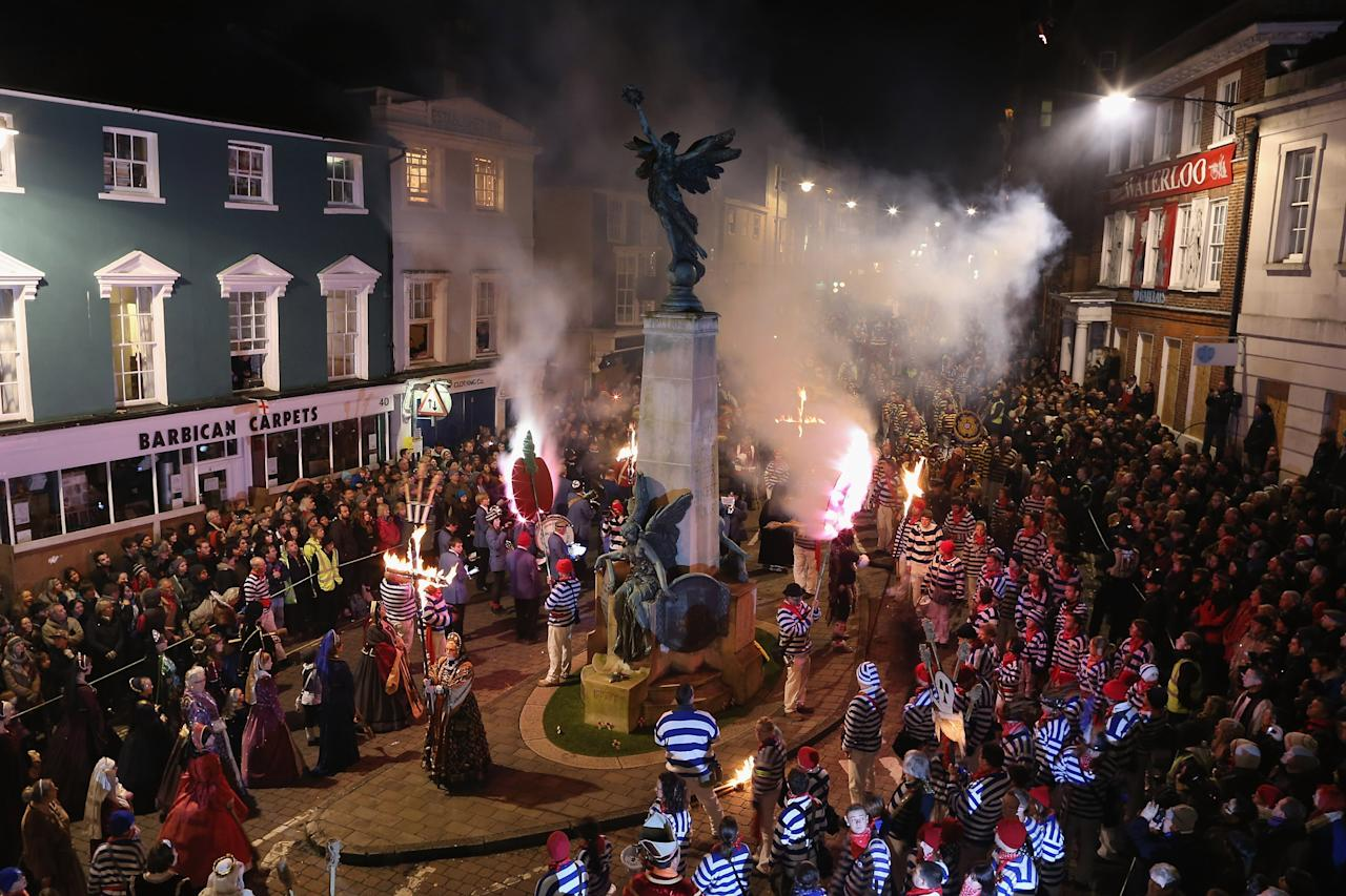 LEWES, ENGLAND - NOVEMBER 05:  Bonfire societies gather around the war memorial for prayers during the Bonfire Night celebrations on November 5, 2012 in Lewes, Sussex in England. Bonfire Night is related to the ancient festival of Samhain, the Celtic New Year. Processions held across the South of England culminate in Lewes on November 5, commemorating the memory of the seventeen Protestant martyrs. Thousands of people attend the parade as Bonfire Societies parade through the narrow streets until the evening comes to an end with the burning of an effigy, or 'guy,' usually representing Guy Fawkes, who died in 1605 after an unsuccessful attempt to blow up The Houses of Parliament.  (Photo by Dan Kitwood/Getty Images)