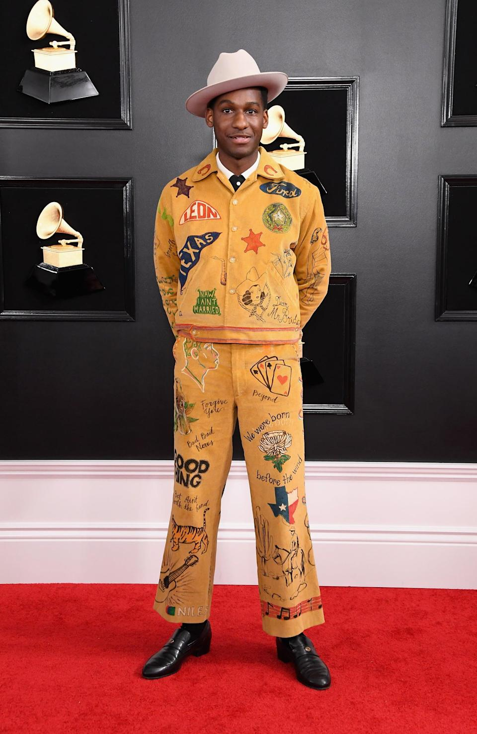 <p>Wearing a mustard graphic-print suit.</p>
