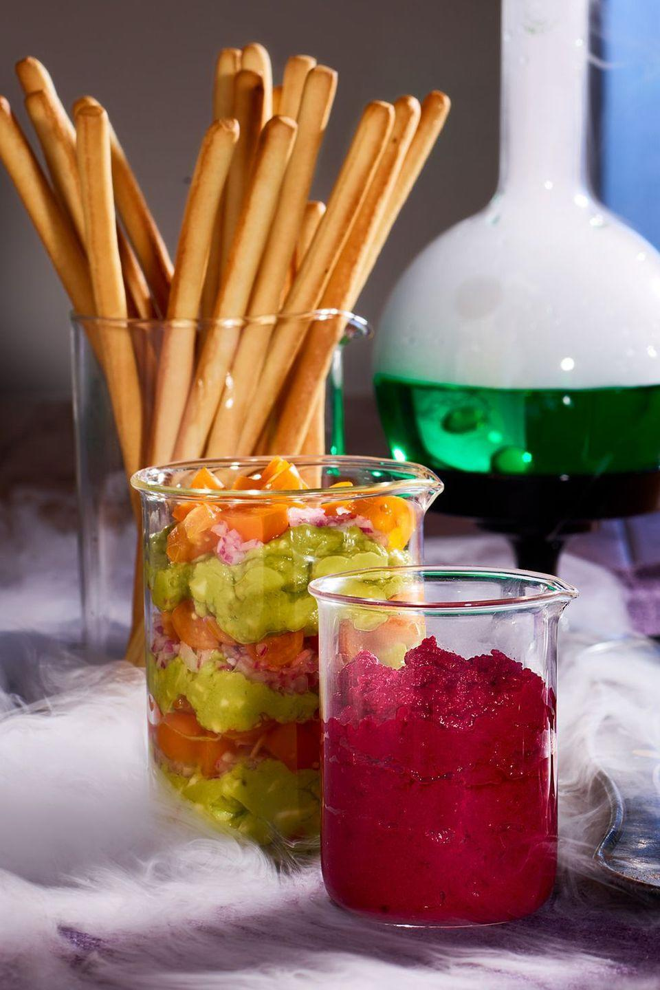 <p>Presentation is everything. This mad scientist display for guacamole, beet hummus, romesco, and bread dips will get guests talking. </p>